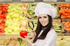 Gelukkige Dame Chef Inspecting Vegetables met Vergrootglas stock foto