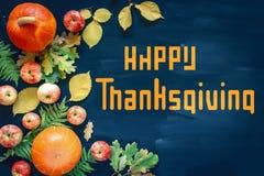Gelukkige Dankzeggingstekst met pompoenen en bladeren over donkere houten achtergrond stock afbeeldingen