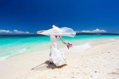 Gelukkige dansende bruid op strand Stock Foto
