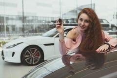 Gelukkige de autosleutels van de vrouwenholding tot haar nieuwe auto stock afbeeldingen