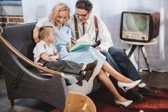 gelukkige de familiezitting van de jaren '50stijl op bank en lezing stock fotografie