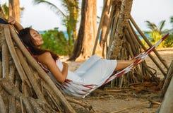 Gelukkige de glimlachvrije tijd van de portret betrekken de mooie jonge Aziatische vrouw op hangmatschommeling rond het strandove stock foto