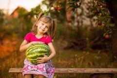 Gelukkige de greep zeer grote watermeloen van het kindmeisje in zonnige dag Gezond concept stock afbeelding