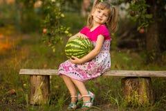 Gelukkige de greep zeer grote watermeloen van het kindmeisje in zonnige dag Gezond concept royalty-vrije stock foto's