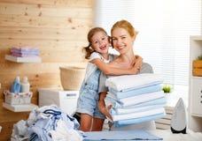 Gelukkige de huisvrouw en het kinddochter van de familiemoeder het strijken kleren stock fotografie