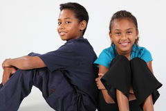 Gelukkige de jongen en het meisjeszitting van schoolvrienden samen Stock Afbeeldingen