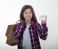 Gelukkige de korting van de klantenholding witte kaart en het winkelen zakken en kartondozen in haar handen Jong meisje met credi stock fotografie