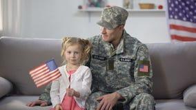 Gelukkige de militair bewonderende dochter die van de V.S. nationale vlag golven, die op bank thuis zitten stock videobeelden
