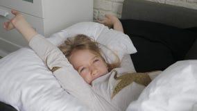 Gelukkige de ontwaken van het meisjeskind het uitrekken zich wapens op het bed in de ochtend Gezondheid, schoonheids en kinderjar stock footage