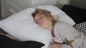 Gelukkige de ontwaken van het meisjeskind het uitrekken zich wapens op het bed in de ochtend Gezondheid, schoonheids en kinderjar stock videobeelden