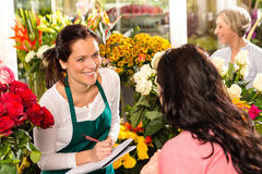 Gelukkige de winkel sprekende klant van de bloemist schrijvende bloem Stock Foto
