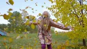 Gelukkige de worp omhoog gele bladeren van het tienermeisje in de langzame motie van het de herfstpark stock video