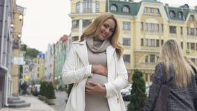 Gelukkige denkende camera bekijken en vrouw die, het strijken buik, moederschap glimlachen stock video