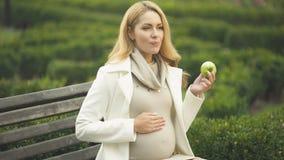 Gelukkige denkende vrouw die groene appel bijten, strijkend buik, moederschapsgezondheidszorg stock videobeelden