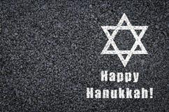 Gelukkige die Chanoeka - ster van David en uitdrukking op asfaltachtergrond wordt geschreven Stock Foto