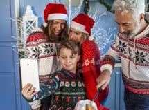 Gelukkige die familie op Kerstmisdag wordt herenigd die een selfie nemen stock afbeeldingen