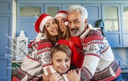 Gelukkige die familie op Kerstmisdag wordt herenigd die elkaar koesteren stock fotografie