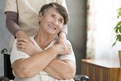 Gelukkige die grootmoeder door verpleegster wordt gesteund royalty-vrije stock afbeeldingen