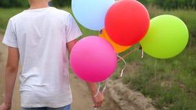 Gelukkige die kinderen op een bosweg met ballons in werking worden gesteld Verjaardagsviering in het Park Gelach en vreugde van k stock video