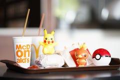 Gelukkige die Maaltijd bij het plastic speelgoed van Mcdonald en van Pokemon wordt geplaatst stock afbeeldingen