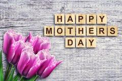 Gelukkige die Moederdag, woord op houten blokken wordt geschreven Mooie Tulpen Houten achtergrond Felicitatie achtergrond De kaar royalty-vrije stock afbeeldingen
