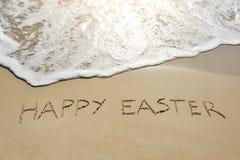 Gelukkige die Pasen op zand wordt geschreven Stock Foto's
