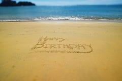Gelukkige die Verjaardag in het gouden zand van Weinig Kaiteri, Nieuw Zeeland wordt geschreven royalty-vrije stock afbeelding