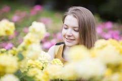 Gelukkige die vrouw door vele gele rozen wordt omringd Royalty-vrije Stock Foto's