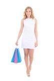 Gelukkige die vrouw met het winkelen zakken op wit wordt geïsoleerd stock foto