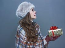 Gelukkige die vrouw op koude blauwe achtergrond wordt geïsoleerd die huidige doos geven Stock Fotografie