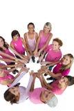 Gelukkige die vrouwen in een cirkel worden aangesloten bij die roze voor borstkanker dragen Royalty-vrije Stock Afbeeldingen