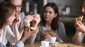 Gelukkige diverse millennial mensengroep die etend pizza in pizzeria spreken stock video