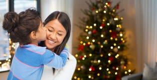 Gelukkige dochter die haar moeder op Kerstmis kussen royalty-vrije stock foto's