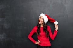 Gelukkige donkerbruine vrouw in rode blouse en Kerstmishoed Stock Fotografie
