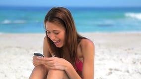 Gelukkige donkerbruine zitting op het zand terwijl het gebruiken van haar cellphone stock videobeelden