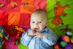 Gelukkige drie van de babymaanden oud jongen, die thuis op kleurrijke a spelen Stock Afbeelding