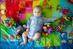 Gelukkige drie van de babymaanden oud jongen, die thuis op kleurrijke a spelen Royalty-vrije Stock Foto