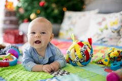 Gelukkige drie van de babymaanden oud jongen, die thuis op kleurrijke a spelen Stock Foto