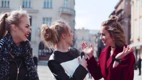 Gelukkige drie vrienden die in het oude stadscentrum wandelen, en lachen gekscheren De vrouw in een rode laag koestert haar vrien stock videobeelden