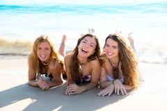 Gelukkige drie vriendenmeisjes die bij strandzand het glimlachen liggen Royalty-vrije Stock Afbeeldingen