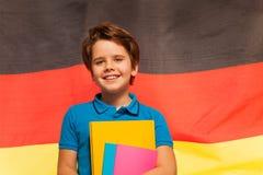 Gelukkige Duitse schooljongen met handboeken in zijn hand stock foto