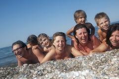 Gelukkige echte mensen die op het strand ontspannen Royalty-vrije Stock Foto's