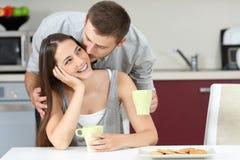 Gelukkige echtgenoot die haar vrouw kussen bij ontbijt Stock Afbeeldingen