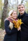 Gelukkige echtgenoot en vrouw met gele esdoorn leafle lach royalty-vrije stock foto's