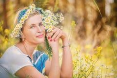 Gelukkige eenvoudige vrouw op een de zomerweide met een boeket van madeliefjes en een kroon van madeliefjes royalty-vrije stock afbeelding