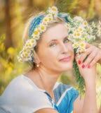 Gelukkige eenvoudige vrouw op een de zomerweide met een boeket van madeliefjes en een kroon van madeliefjes royalty-vrije stock afbeeldingen