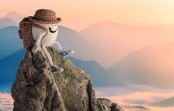 Gelukkige eiwandelaar in een grappige hoedenzitting op een klip stock foto's