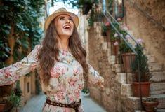 Gelukkige elegante reizigersvrouw in zich het oude Italiaanse stad verheugen royalty-vrije stock foto