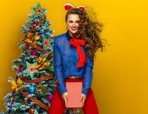 Gelukkige elegante vrouw dichtbij Kerstboom met boek het springen royalty-vrije stock fotografie
