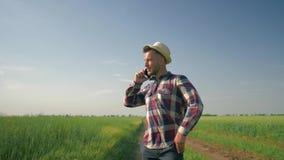Gelukkige emoties terwijl het spreken op mobiele telefoon, landbouwer in strohoed en geruit overhemd die langs een landweg binnen stock footage